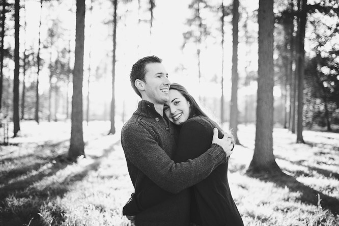 engagement shoot in the winter nadia and dan smiling in the woods