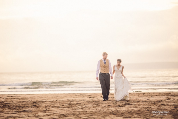 lucy and tim walking on the beach at their wedding in devon