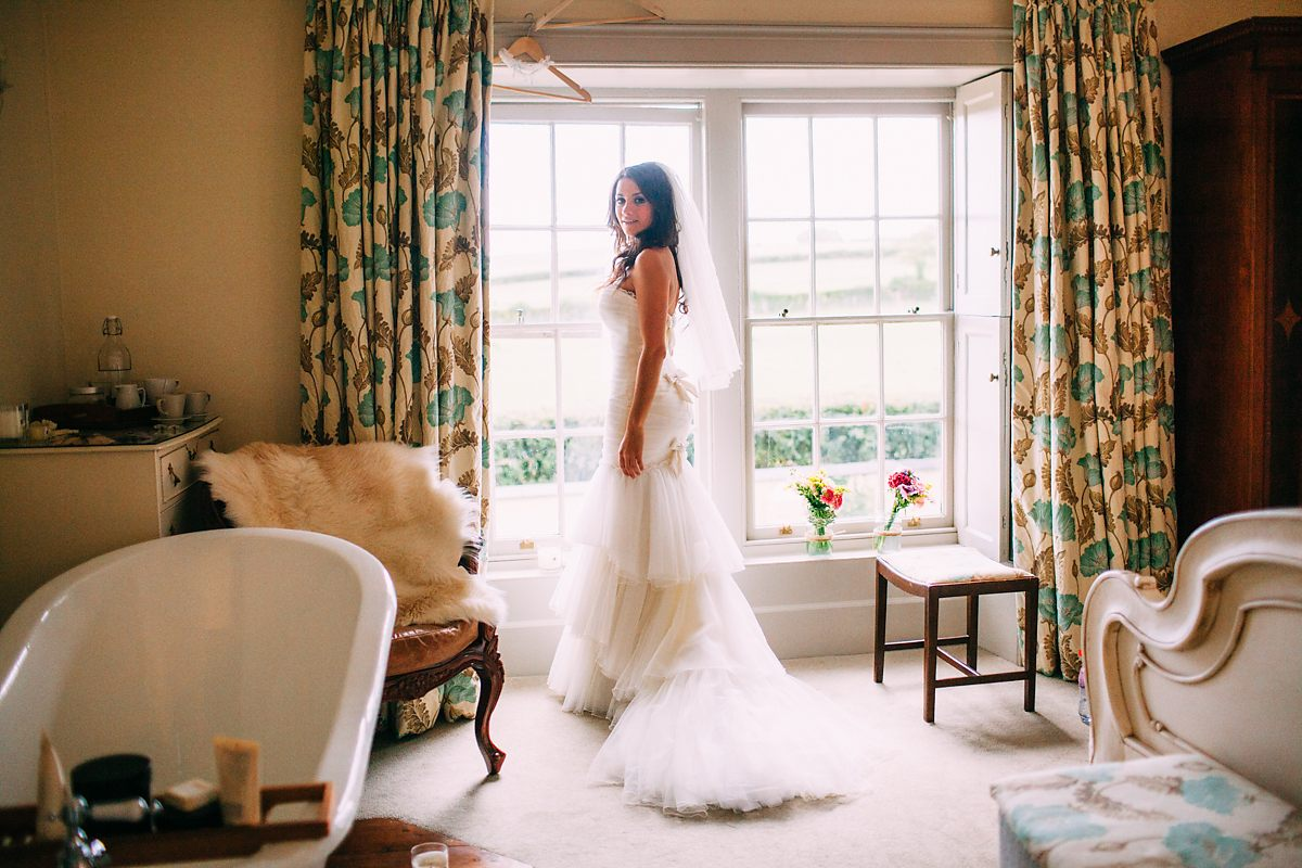 bride standing in window before wedding natural