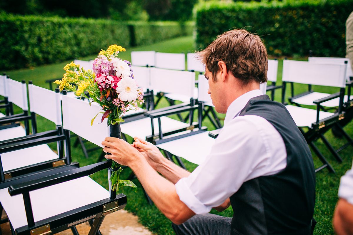ushers tying wedding flowers to the chairs