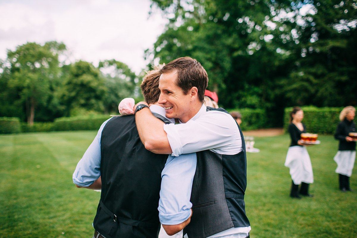 groom and friends hugging after the wedding ceremony