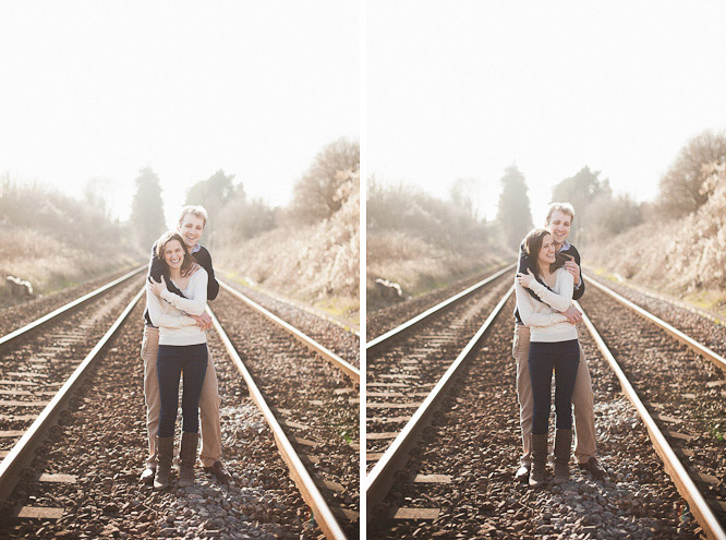 lucy and tim laughing on train tracks in the springtime