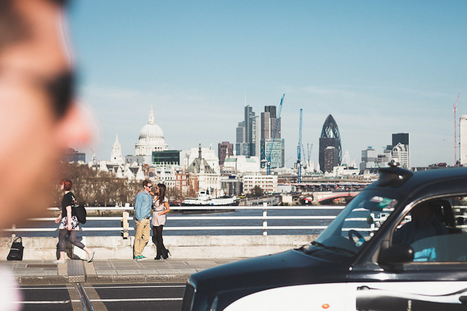 crowded photo of couple on waterloo bridge in london with the gherkin in the background along with st pauls