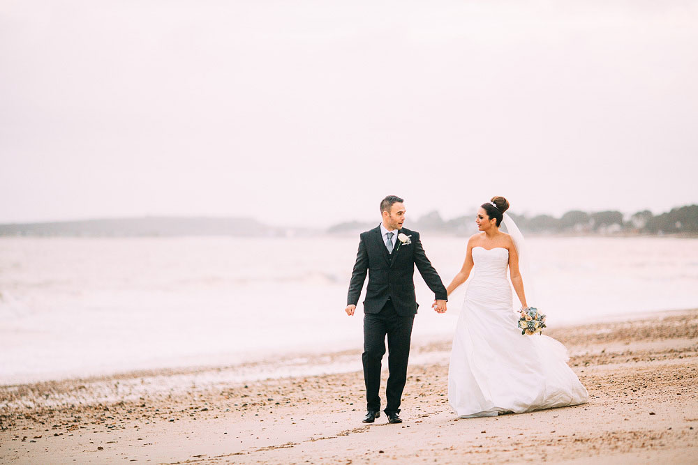 couple walk along the beach at Highcliffe Castle Wedding
