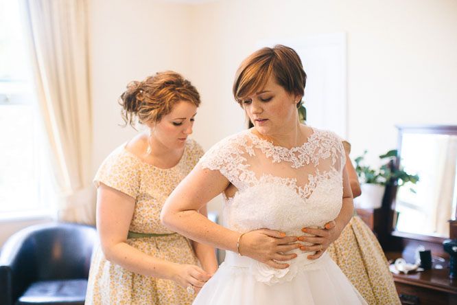 bride getting in to her dress before the wedding in lyde court