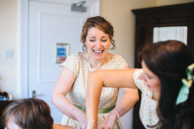 bridesmaids laughing putting bride in to dress