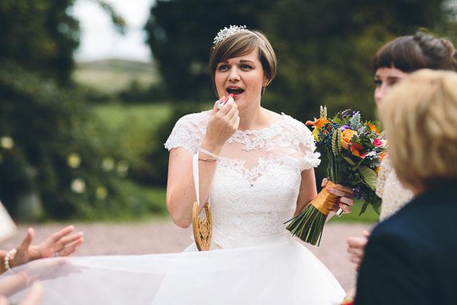 creative wedding photo of bride putting on her lipstick