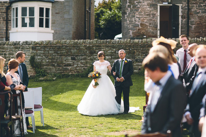 bride walking down the wedding aisle with her father summer wedding
