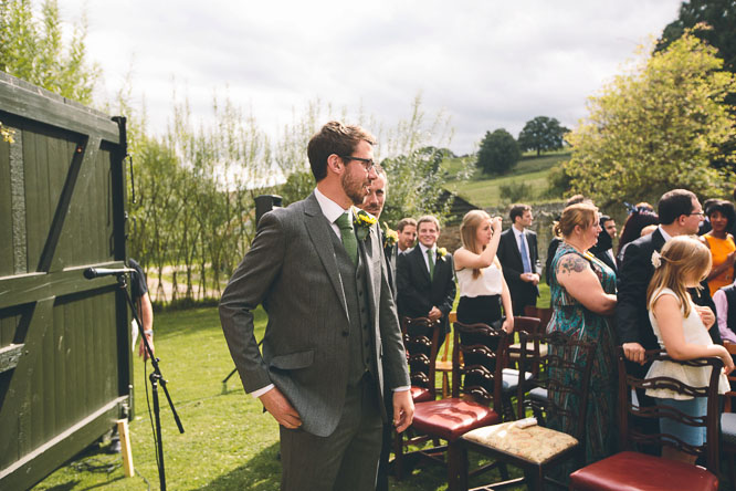 groom watching bride walk down the aisle of Lyde Court