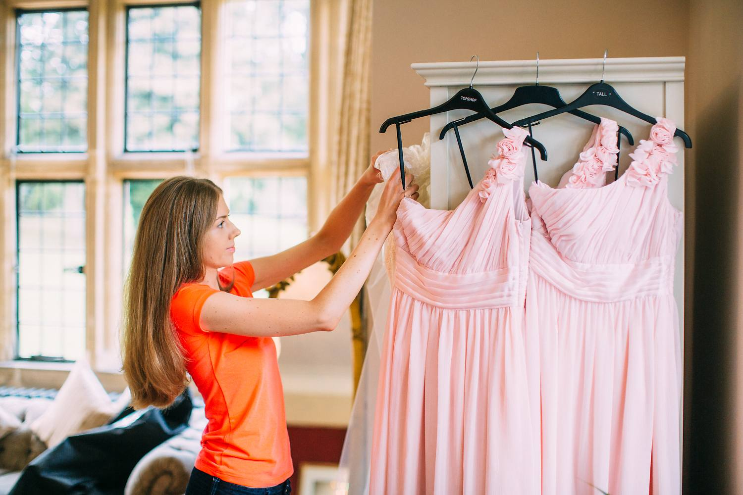 bride hanging up pink bridesmaid dresses