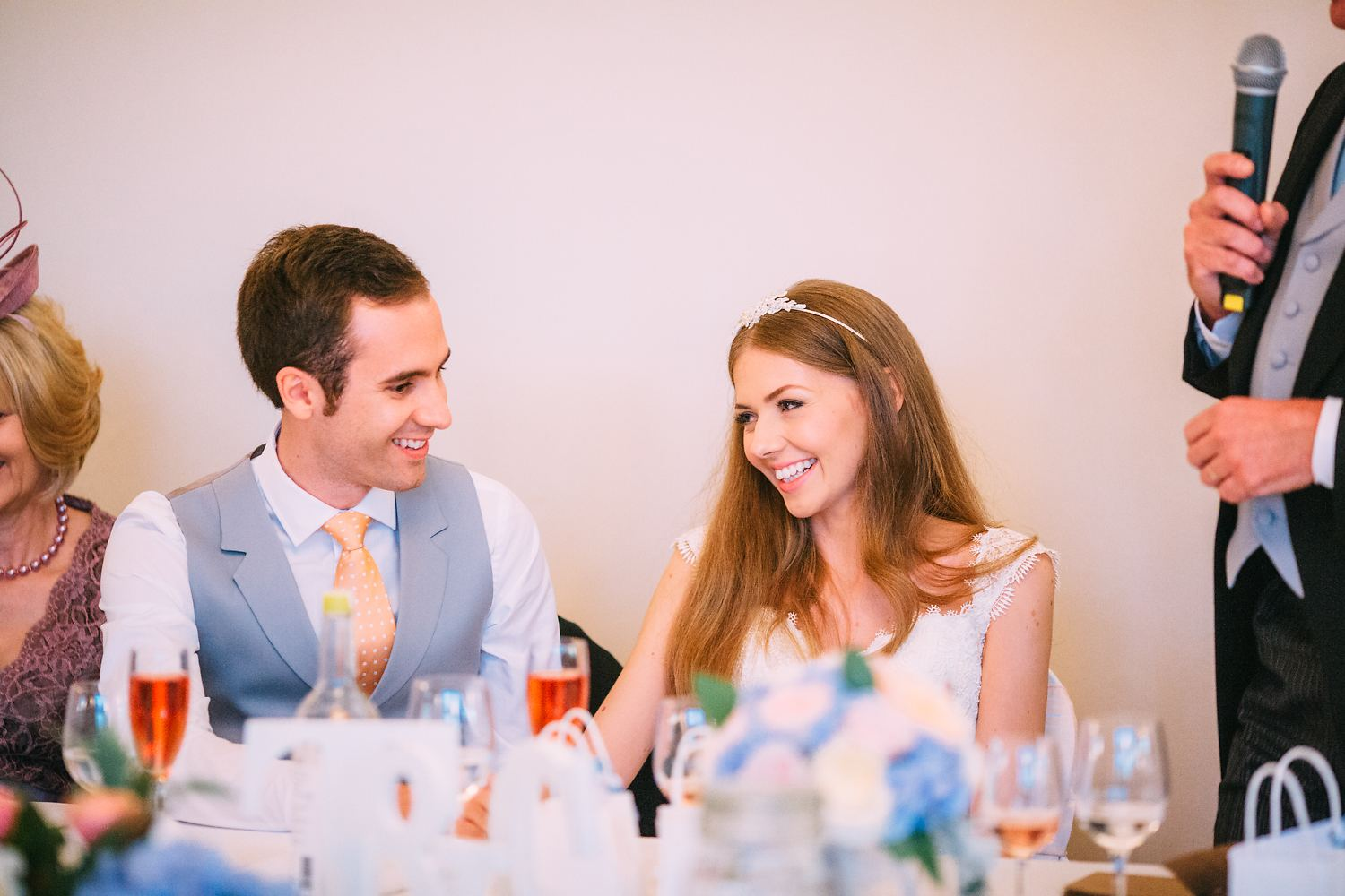 bride and groom laughing at speech