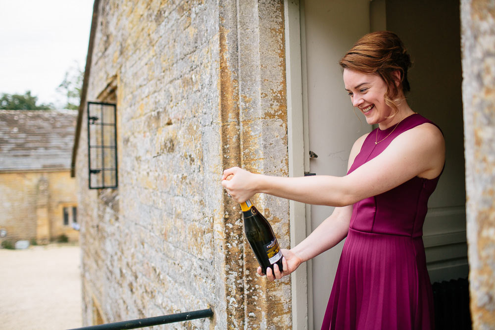 bridesmaid opening the wedding champagne