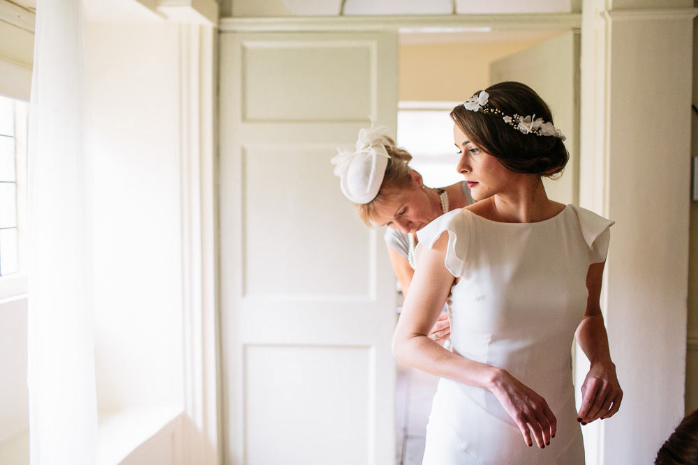 bride getting in to her wedding dress ay Brympton House
