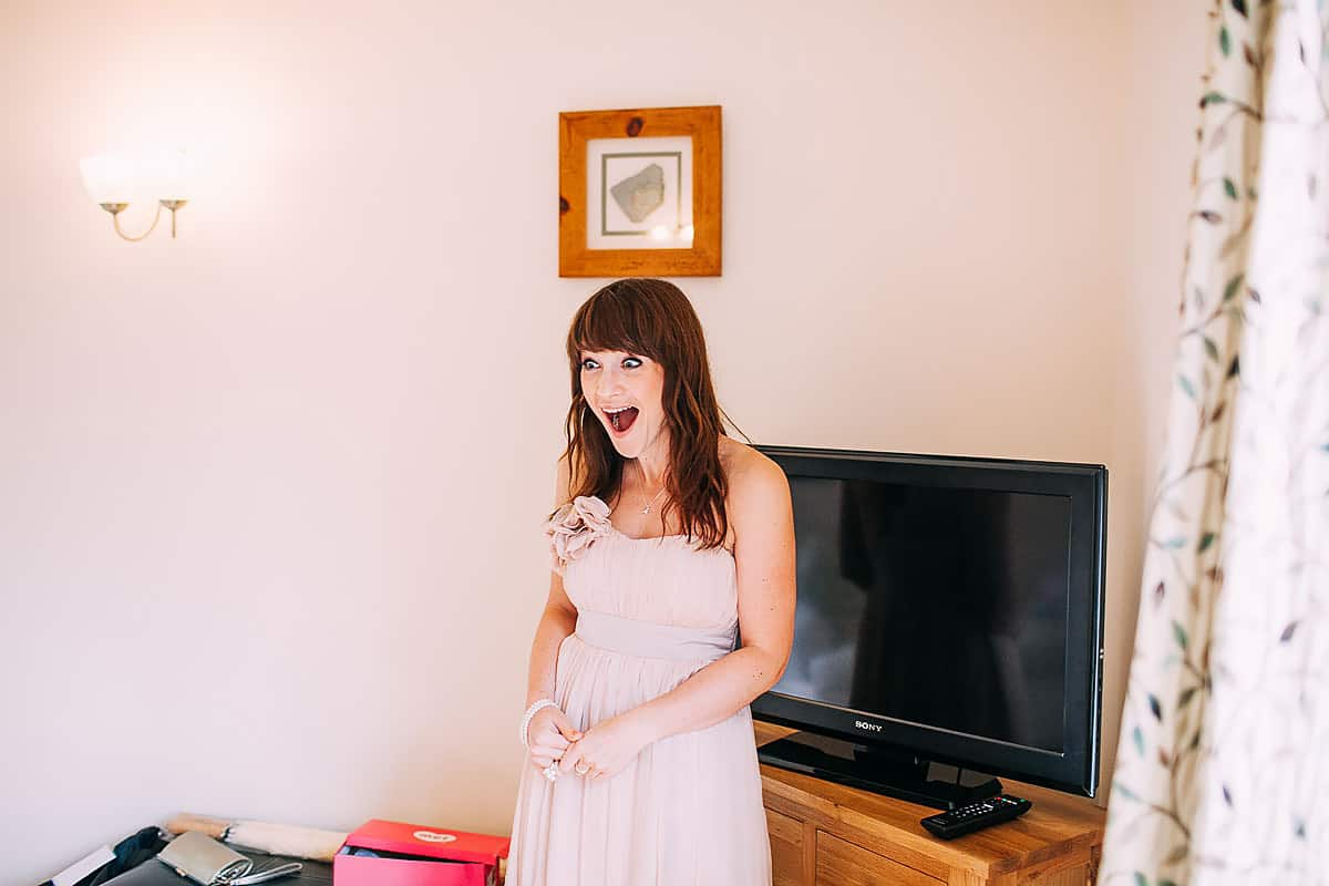 bridesmaid reacting to bride in dress