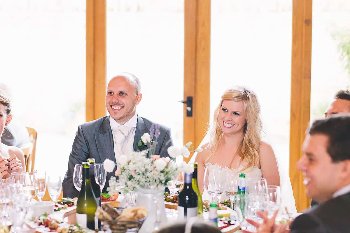 bride and groom smiling at Kingscote Barn