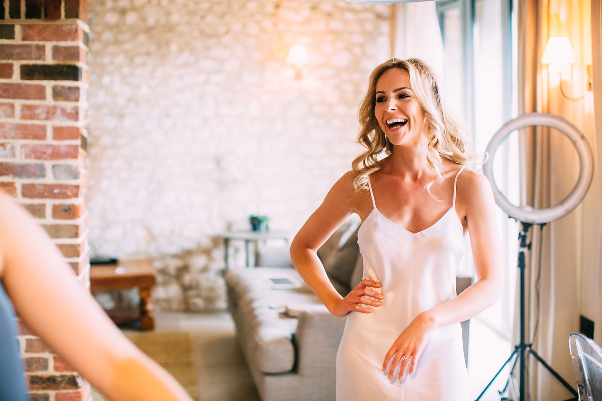 happy bride laughing at lulworth castle getting ready photos