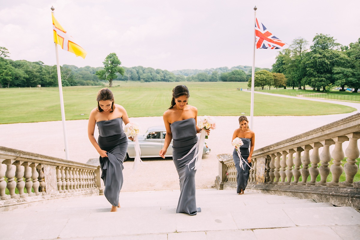 bridesmaids walking up the steps of lulworth castle
