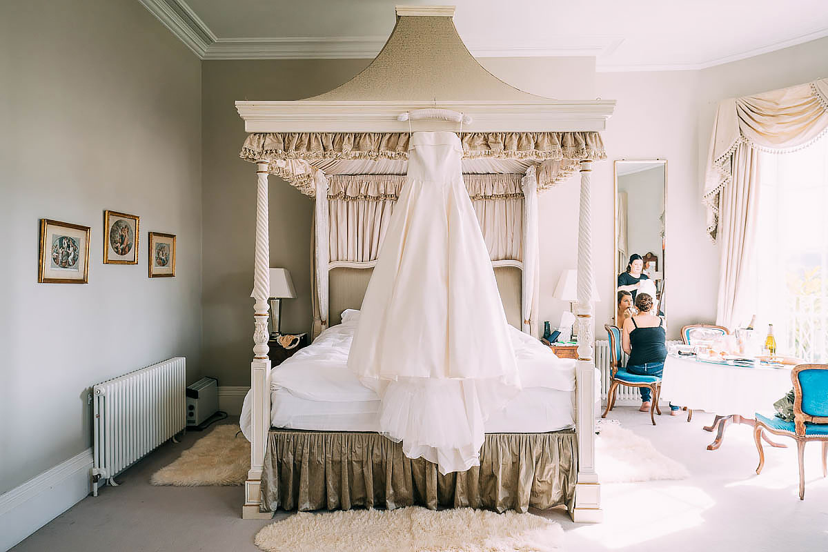 brides wedding gown hanging up in bedroom