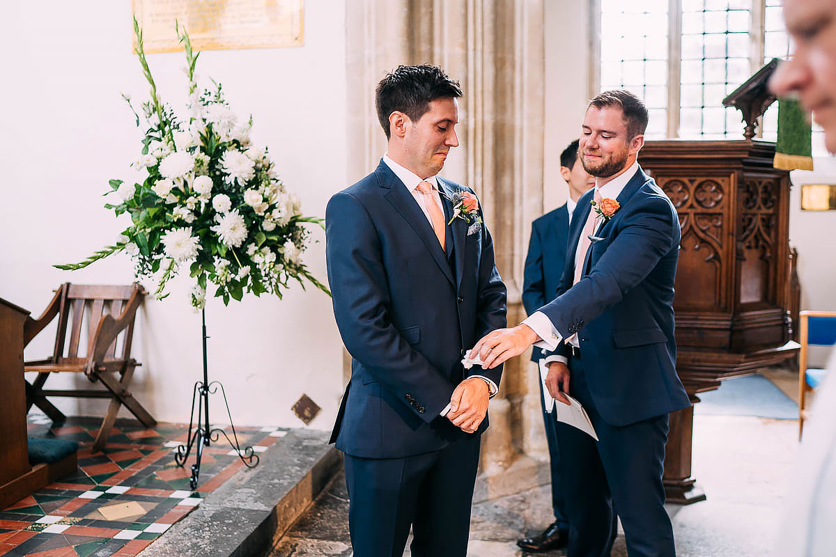 groom being passed a tissue inside church
