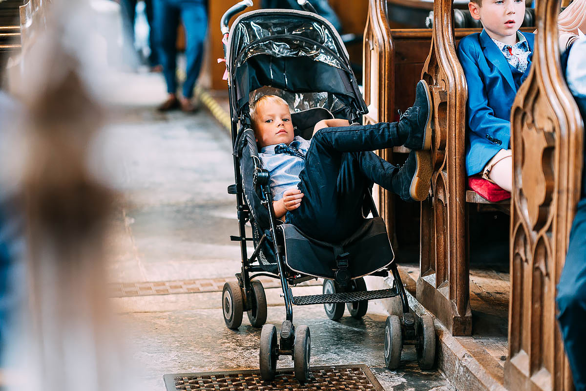 bored child in pushchair at wedding