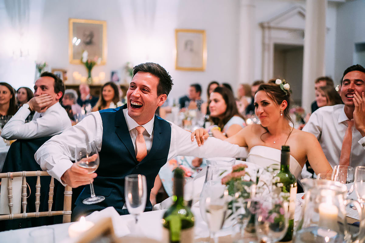 groom reacting to wedding speech