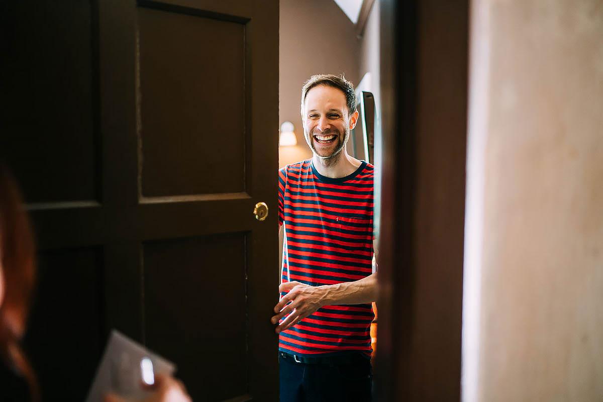groom opening the door and smiling