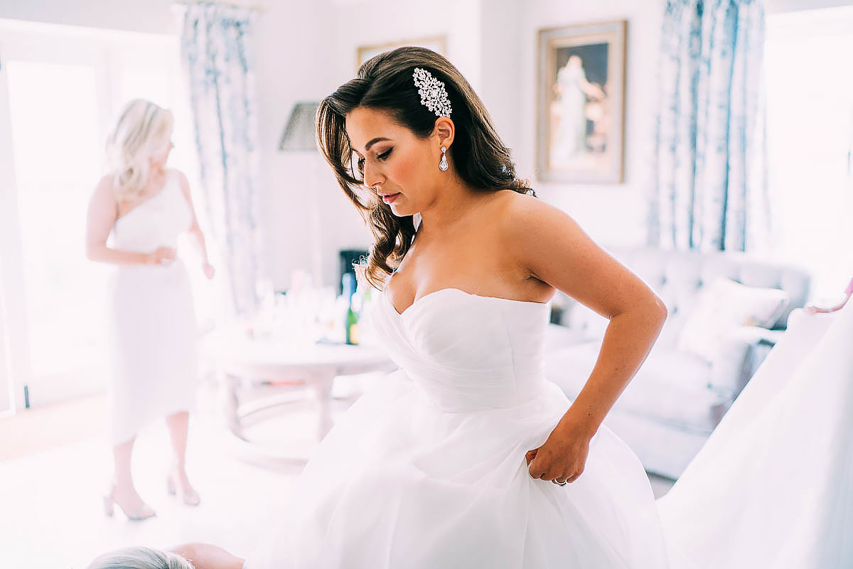 bride getting in to wedding dress