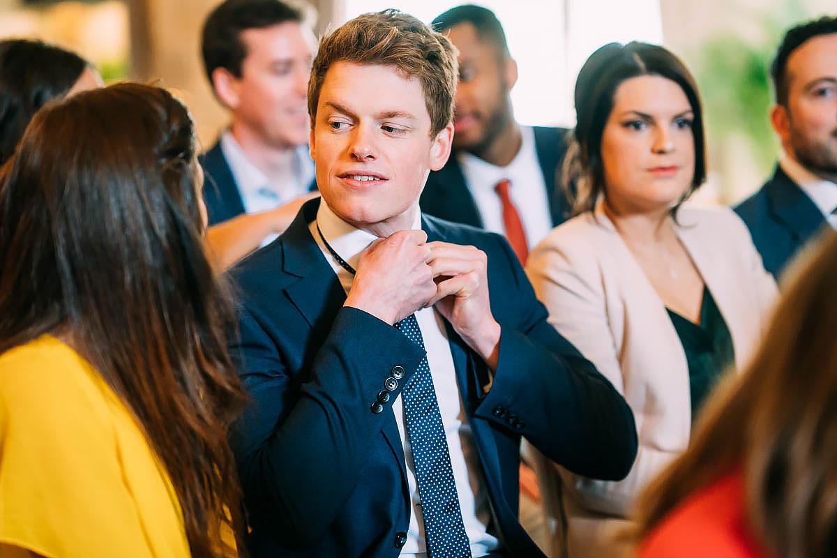 wedding guest tying tie