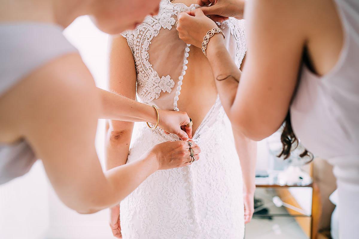 bridesmaids putting on wedding dress