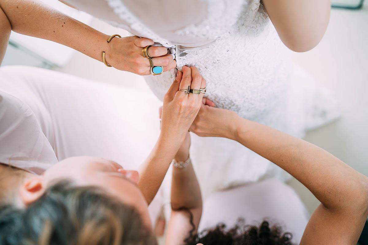 wedding dress being fastened