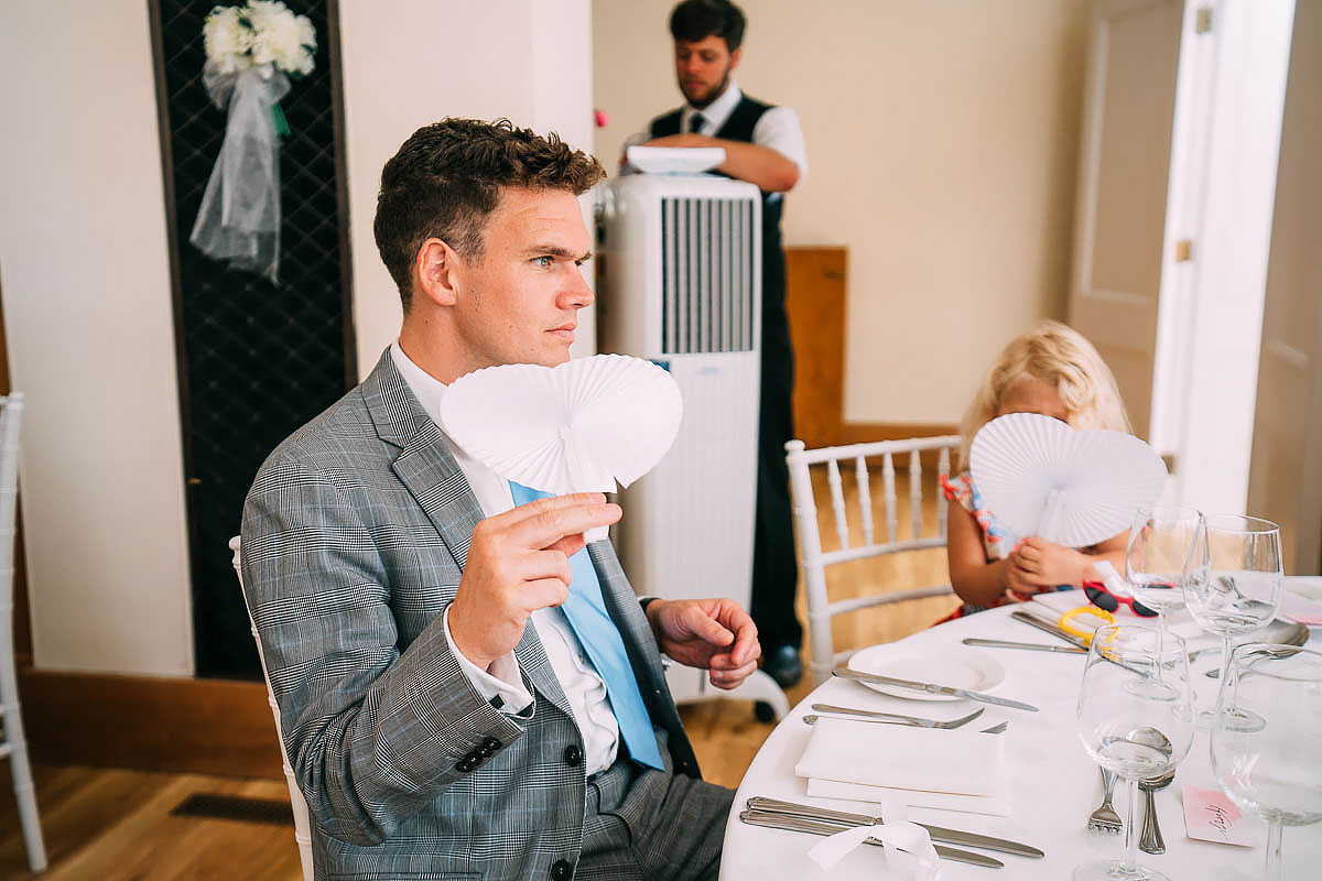 hot guest using fan at wedding