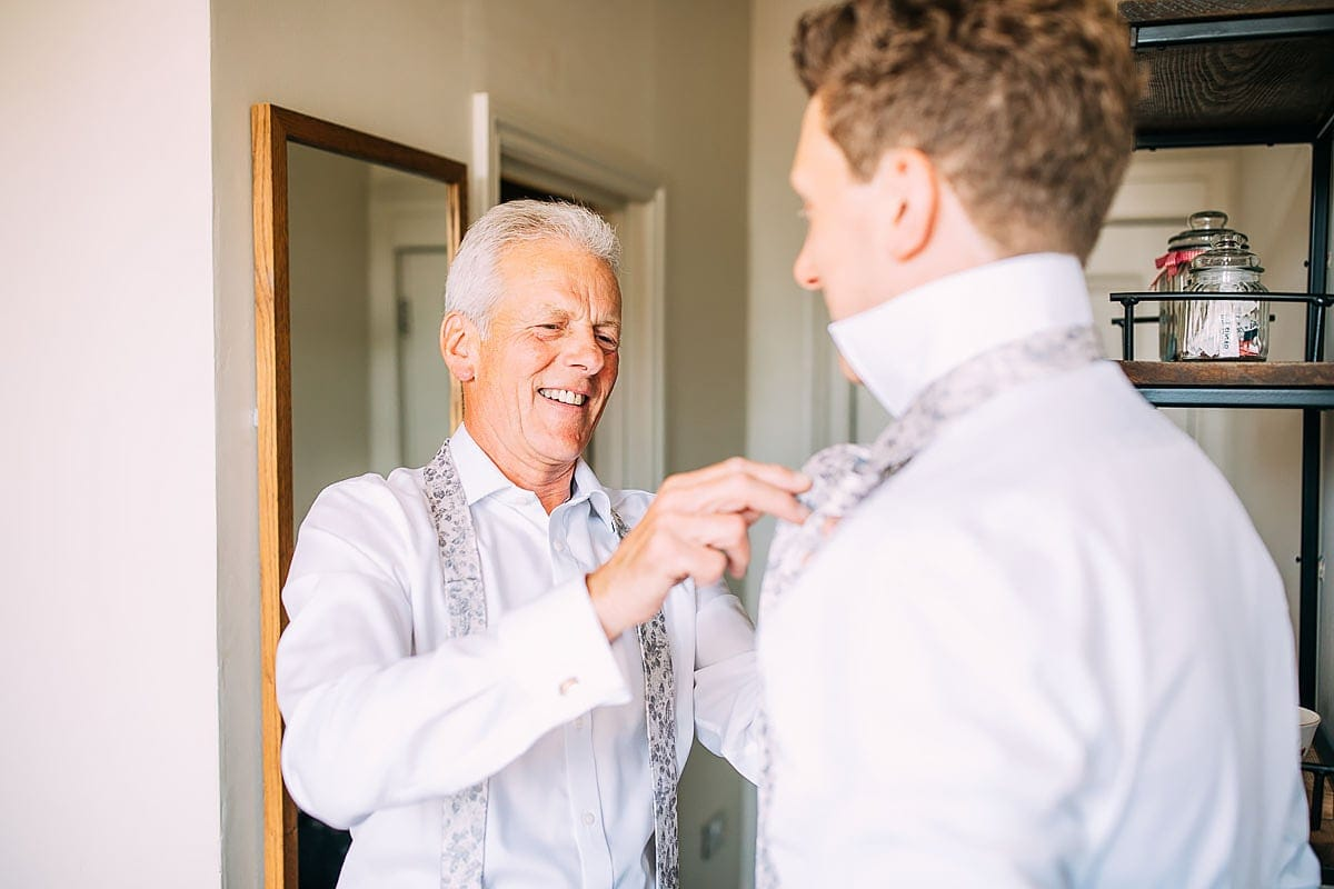 father of the groom putting on tie