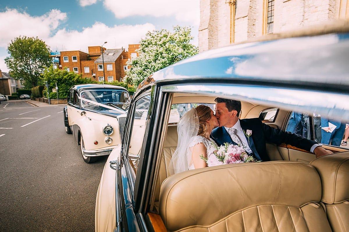 bride and groom kissing in wedding car