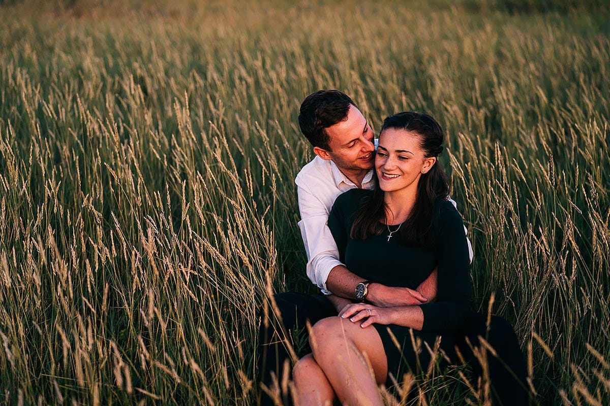 couple sat in grass at sunset