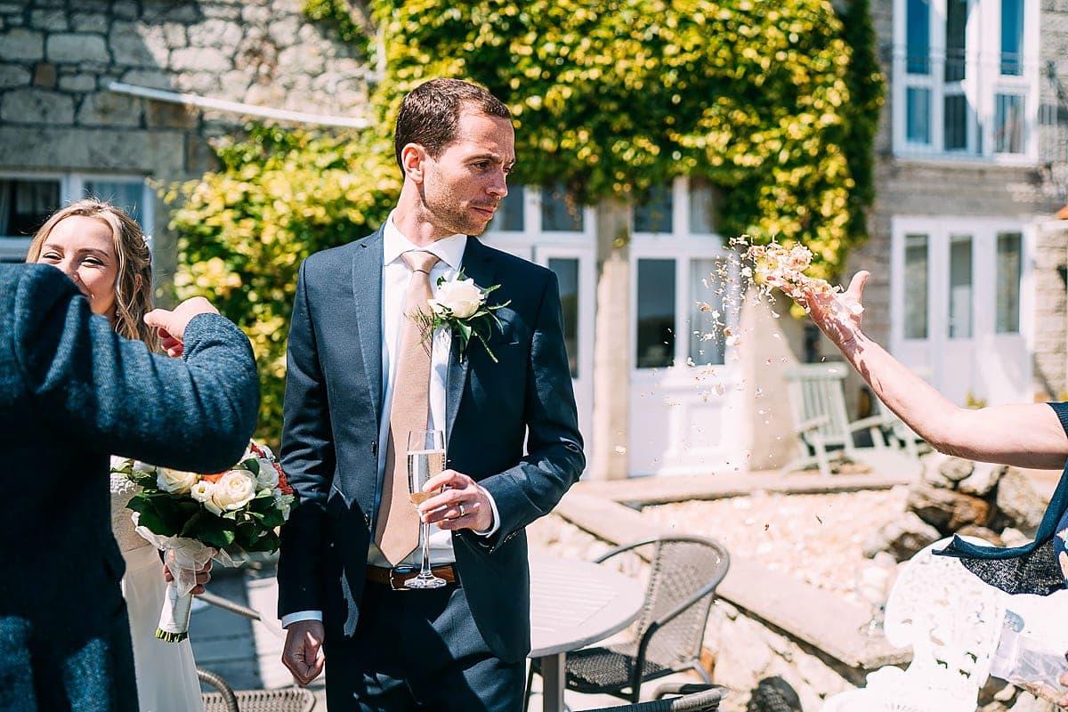 hand throwing confetti on groom